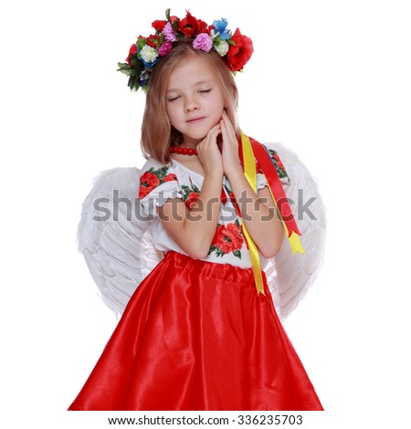 Emotional little angel in a beautiful Ukrainian costume as a symbol of keeper of country on a white background - stock photo