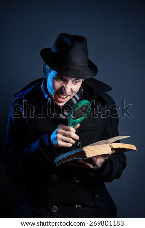 Emotional man in black hat with magnifier glass reading the old book at dark background - stock photo