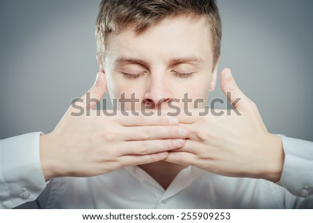 Emotional man keep his mouth closed by his hands - stock photo