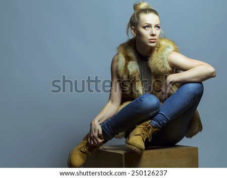 Emotional portrait of a gorgeous fashion blond model in blue jeans and casual waistcoat posing over blue background.  Studio shot. Hipster style. Copy space - stock photo