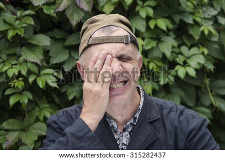 Emotional portrait of a man, covering his face by hand while his eyes are shut - stock photo