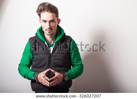 Emotional portrait of attractive young man in a grey vest & green sweater with a hood. Studio photo.  - stock photo