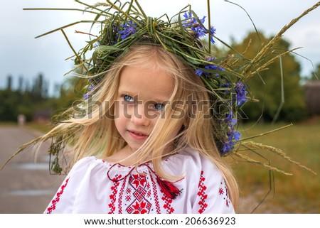 Emotional portrait of ukrainian girl in flower chaplet - stock photo