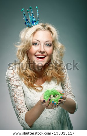 emotional portrait of woman wearing  blue princess crown and holding nest with quail eggs - stock photo