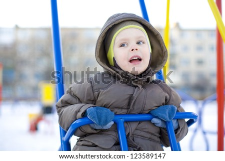 Emotional small child riding on a swing - stock photo