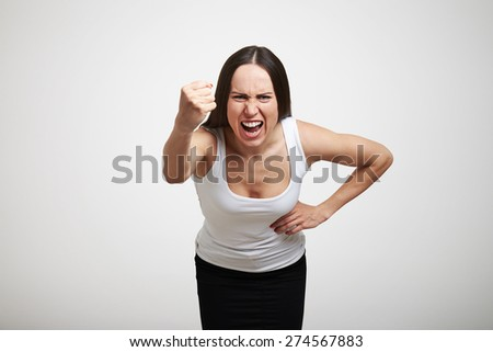 emotional woman yelling, looking at camera and waving her fist. isolated on light grey background - stock photo