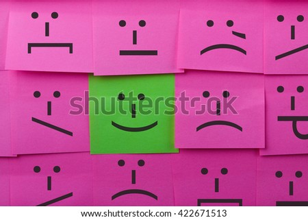 Emotions concept. Background of sticky notes. Green sticky note is among pink sticky notes. - stock photo
