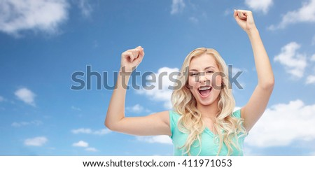 emotions, expressions, success and people concept - happy young woman or teenage girl celebrating victory over blue sky and clouds background - stock photo