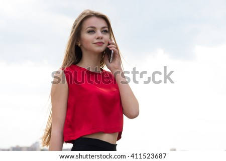 emotions, expressions, technology and people concept - smiling young woman or teenage girl texting on smartphone over blue sky and clouds background - stock photo