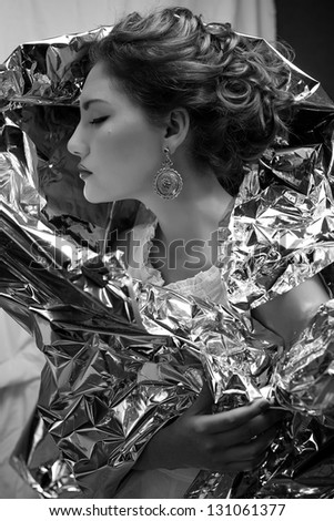 Emotive arty portrait of a fashionable queen-like young woman in white vintage dress posing over wrinkled foil background. Perfect retro hairdo. Close up. Profile. Black & white studio shot - stock photo