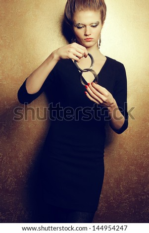 Emotive portrait of a beautiful fashion red-haired model with a great makeup of golden foil posing over golden background and playing with her golden bracelet. Studio shot - stock photo