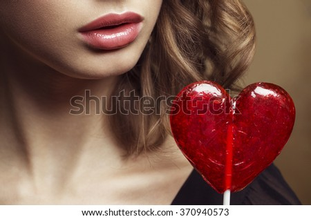 Emotive portrait of a beautiful fashion red-haired model with a natural makeup posing over golden background, holding in her hand red heart-candy. Retro style hairdo. Studio shot. Close up photo - stock photo