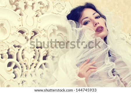 Emotive portrait of a beautiful queen like girl (bride) in classic white dress posing in her white vintage bedroom. Retro style. Close up. Copy-space. Studio shot - stock photo