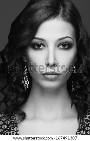 Emotive portrait of a fashionable model with curly glossy hair and evening make-up posing over grey background. Silver earrings. Perfect healthy skin. Retro (vintage) style. Close up. Studio shot - stock photo