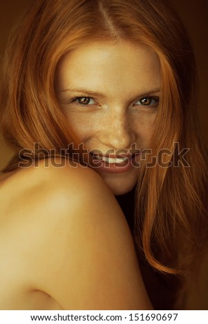 Emotive portrait of a fashionable model with red (ginger) wavy hair and natural make-up. Great white shiny smile. Perfect skin with freckles. Retro style. Close up. Studio shot - stock photo