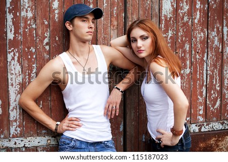 emotive portrait of a stylish couple in jeans standing near wooden house. outdoor shot - stock photo