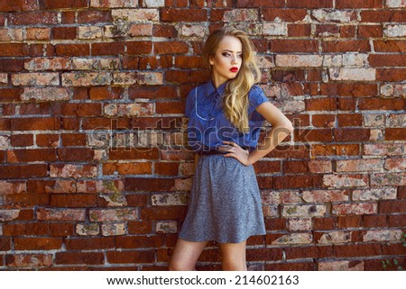 Emotive portrait of a young beautiful blond-haired girl wearing trendy blue shirt and grey skirt, posing over old bricken wall. . Healthy skin with freckles, glossy hair. Outdoor shot - stock photo