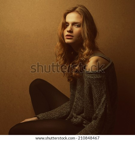 Emotive portrait of fashionable model with long curly red hair and natural make-up posing over wooden background. Perfect skin. Urban grunge style. Studio shot - stock photo