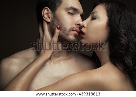 Emotive portrait of two lovers over chocolate background - handsome man and gorgeous woman with perfect hair and skin. Pure passion. Close up. Studio shot - stock photo