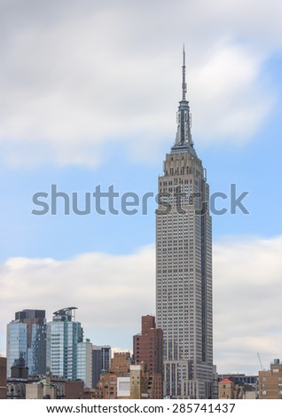 Empire state building by day, white clouds and blue sky in the background - June 3, 2015, Manhattan, New York City, NY, USA - stock photo