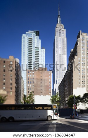 Empire State Building in New York with deep blue sky. Shot with a tilt and shift lens with selective focus on the Empire State. - stock photo