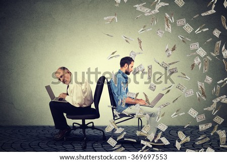 Employee compensation economy concept. Senior man working on laptop sitting next to young entrepreneur guy using computer under money rain. Pay difference concept.  - stock photo