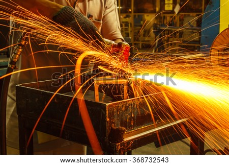 Employee grinding industry automotive parts,with sparks  - stock photo