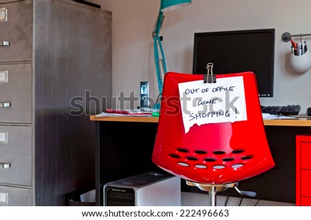 Employee leaves note on back of office chair: Out of Office. Gone Shopping! - stock photo