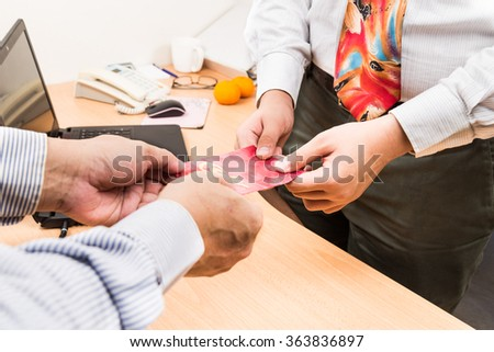 Employee receiving red packet with Good Fortune Chinese wordings, from employer upon returning to work in office - stock photo