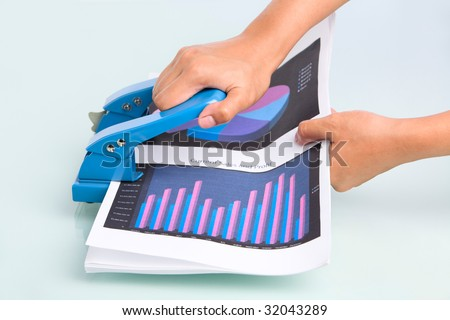 Employee's hand is ready to press hole puncher where the document placed in. Taken from side view - stock photo