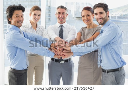 Employee's smiling and having fun while stacking hands together - stock photo
