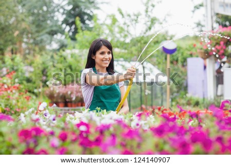 Employee watering plants with hose in garden center - stock photo