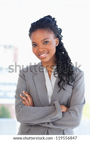 Employee wearing a formal business suit while crossing her arms - stock photo