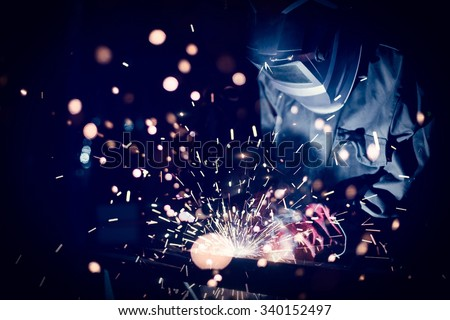 Employee welding steel with sparks using mig mag welder - focus on sparks. - stock photo