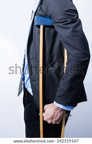 employee with crutches, white background. - stock photo