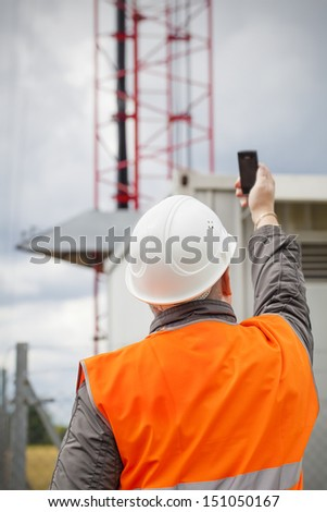 Employee with the cell phone near to gsm tower before the rain - stock photo