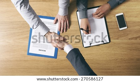 Employer hiring and giving an handshake to the candidate after the job interview, hands close up top view - stock photo