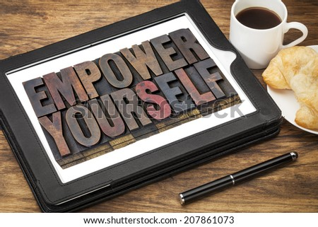 empower yourself - motivation concept - text in vintage letterpress wood type blocks stained by ink on a digital tablet with cup of coffee - stock photo