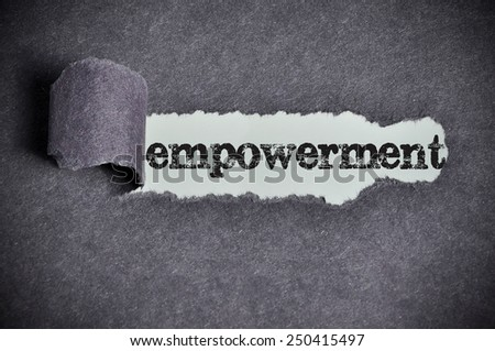 empowerment  word under torn black sugar paper  - stock photo