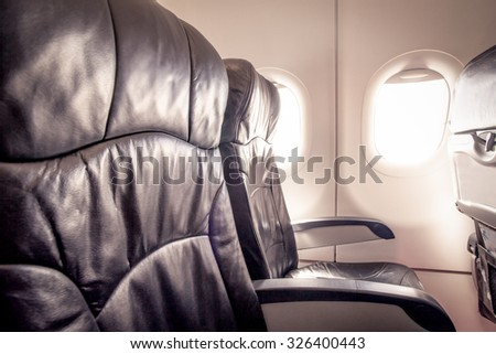 Empty airplane seats and window in the cabin - stock photo