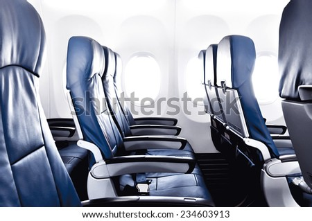 Empty airplane seats in the cabin - stock photo