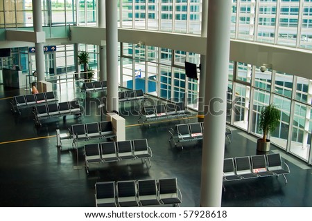 empty airport terminal waiting area with chairs - stock photo