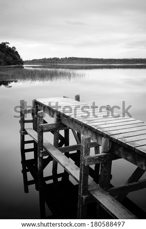 Empty and serene jetty on a moody winters day in black and white - stock photo