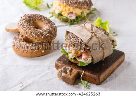 Empty and staff sprinkle seeds Whole Grain bagels with scrambled eggs, pea sprout, fried onions and prosciutto ham, making on white linen tablecloth and small wooden chopping board. - stock photo