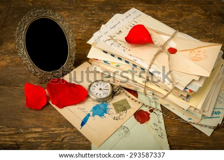 Empty antique picture frame and a pile of old letters on a wooden table - stock photo