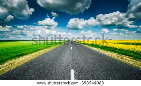 Empty Asphalt Countryside Road Through Fields With Yellow Flowering Canola Rapecolza And Growing Green Wheat In Spring. Sunny Day White Clouds On Blue Sky. Panorama - stock photo