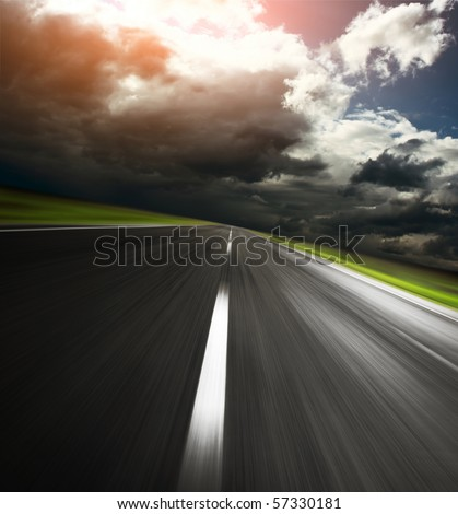 Empty asphalt road and cloudy sky with sunlight - stock photo