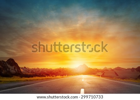 Empty asphalt road and sun rising at skyline - stock photo