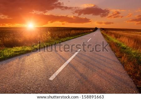 Empty asphalt road at sunset - stock photo