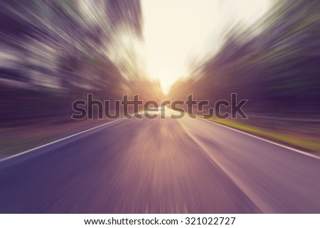 Empty asphalt road in motion blur and sunlight with vintage tone. - stock photo